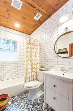 The hall bathroom has so much character using Spanish tile patterned floor tiles, white subway tiles with black grout, an ikea vanity, and a gold mirror. But what really makes the bathroom interesting is the original wood shiplap ceiling.  It was exposed since the drywall had fallen down.