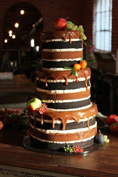 Naked Tuxedo cake from Superfine Bakery featuring caramel drips, real fruit, and sculpted marzipan fruit.