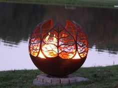 Autumn Sunset 37″ Leaf Fire Pit Sphere. Leaf designs surround this unique artisan fire bowl and features an open top and flat steel base.  It