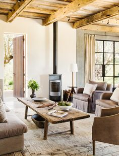 Taupe couch and sofa chair, wood coffee table, printed tan rug, and wood door