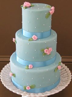 Feminine and romantic blue wedding cake with tiny pink roses scattered among the dotted tiers. Beautiful cake.  ᘡղbᘡ