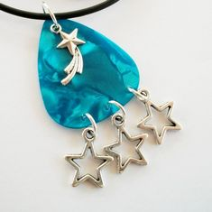 A blue guitar pick with stars on a necklace.
