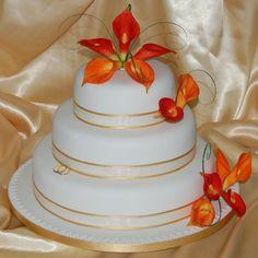 Mango colored calla lilies on white wedding cake