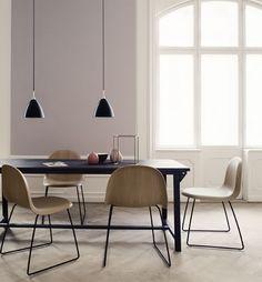 Dunkler, schlichter Holztisch und leichten, hellen Schalenstühlen auf Metallbeinen, alles von Gubi.