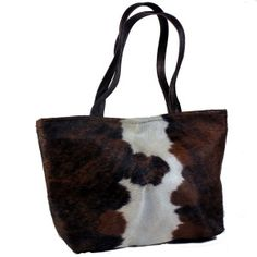 """Brown and White Hair on Cowhide tote Brown leather handles. Interior with 3"""" leather top and beautiful cotton floral lining .One leather zippered interior pocket and 2 open hand beaded, fabric pockets. Leather strap with brass toggle for easy to find keys. Magnetic closure. 18""""wide x 12"""" high with 5"""" soft bottom."""