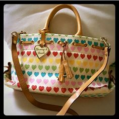 Genuine Dooney & Bourke Heart bag Adorable Dooney & Bourke heart bag. Made of canvas and leather. Hearts are in different hues of the rainbow with a cream background. It has four small interior Pockets. Genuine Dooney & Bourke that has been retired and no longer made. Purse is in great condition! One tiny spot as shown in picture number 2 and slight discoloration of the strap as seen in picture number 4. Otherwise there are no other flaws. This bag is whimsical and fun and I'm looking to get…