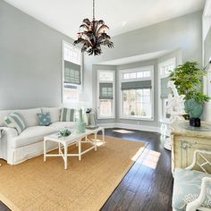 Walls are Sea Salt by Sherwin Williams - SW6204. A light gray-blue on the walls will keep the room feeling light and happy, but is a more kid-friendly option than bright white. Sunroom, beach-style family room.