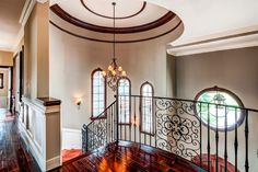 Traditional Staircase with Crown molding, High ceiling, Chandelier, Hardwood floors, Arched window, Wall sconce