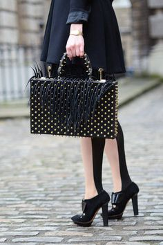 Londoners are known for their eccentric accoutrements like this statement bag and pair of two-tone tights.    - ELLE.com