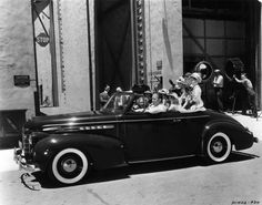 Bing Crosby giving rides around the studio lot in his 1939 Olds coupe convertible
