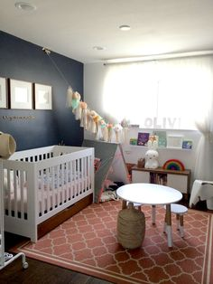 Attractive Nursery Rooms With Whimsical Decors : Fascinating Whimsical Nursery Room Decor with Navy Blue Wall Painting and White Baby Crib also White Round Table and Attractive Pattern Rug