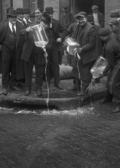 Pouring bootleg whiskey into the street, 1931