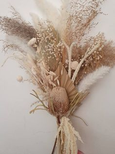 A stunning dried arrangement that looks at home anywhere! This is such a beautiful bouquet from the fluffy reeds to the palms to the hanging white amaranthus to hang down the side of the vase, this arrangement is sure to be very pleasing on anyone's eyes!This arrangement is now available in a small (photos 6, 7 and 8 ) and large (photos 1, 2 ,3 ,4 and 5 ), large is around 80cm tall from stem to tips and the small is around 60cm tall from stem to tips. Large is a fuller version while small is…