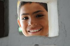 César, 12, a sixth-grade student, smiles as he peers through a cement block window of a classroom at La Unión Educational Institute Secondary School in Lorica, Columbia. Children at the school have been affected, and many displaced, by recent flooding. UNICEF has supported an initiative to adjust the school year calendar around peak seasonal rains, and to ensure that alternative shelters, rather than schools, are available in the event of flooding © UNICEF/Susan Markisz http://www.unicef.org