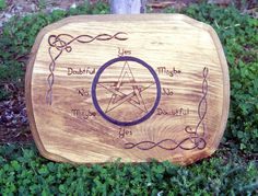 """Beautiful Pendulum Board/Talking Board. Pendulum's are a useful tool for any magickal practitioner. One of the best ways to use a pendulum is with a pendulum board. Pendulum boards and talking boards allows a more structural communication with the inner and outer divine. This on is hand drawn and hand burned. Measures 11 1/2""""x 8 3/4"""". Stained a golden oak that really allows the grain of the wood to come through. Sealed for protection."""