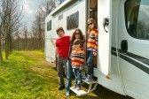 Family vacation in camping  Happy active parents with kids travel on camper  RV   Family having fun near their motorhome