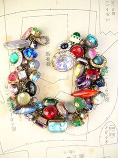 Double Stuff Random Color Vintage Button Bracelet #3 This bracelet has all vintage rhinestone buttons in various colors in random order. There are so many different varieties and sizes, some with lacy bezels, some with clean setting and no prongs, some with gold tone settings, all with various signs of age (which we love!)!   BUT.... I make a lot of these vintage rhinestone button bracelets and everyone loves them. Normally, they have about 25 buttons depending, one on every other loop of…