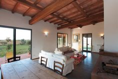"""House in Tuscania, Italy. The White Farm, Podere S. Antonio, is located on a hilltop overlooking a """"breathtaking view"""" of the countryside with the sea on the horizon. The house is surrounded by olive trees and wheat fields. Fig, apricot, plum and jujube trees surround the ..."""