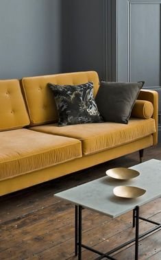 The Porto three-seater sofa in honey yellow velvet. Drawing inspiration from luxury mid-century living, the Porto's clean-lined shape gives it a super sophisticated look, while defining details like its buttoned back, loose bolster cushions and brass-capped feet add a layer of opulence.