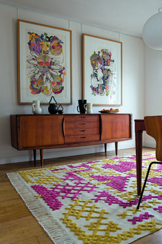 Mid-century modern furniture, abstract collage paintings and cross-stitch inspired rug
