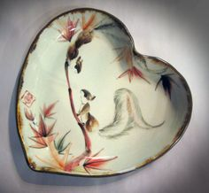 A squirrel pair share a passionate gaze on a high-fire stoneware dish shaped in a heart. Brushpainted with maple leaves which represent compatibility and companionship by Tracie Griffith Tso of Reston, Va.