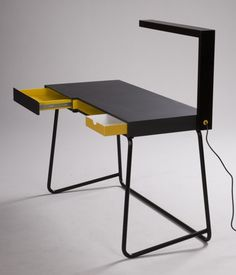 Frank Desk by John Slater, Britain. Wrap-around edge that swings up to reveal storage, with the edge itself being a light. Neat treatment of edges and negative space.