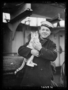 Sailor from HMS Exeter holding Pincher - ship's cat and mascot (February 15, 1940) - Photograph taken by Harold Tomlin for the Daily Herald newspaper