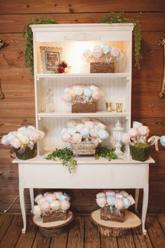 """Cotton Candy Wedding Favors on Vintage Hutch  The guests were given whimsical cotton candy lollipops as their wedding favors. A label with """"Thanks for making our day so much sweeter,"""" was placed on each blue raspberry, pina colada or pink vanilla flavored confection. """"I wanted a fun foodie gift that showed our playful side. They were displayed at the front of the barn,"""" says Nikole. For their guests preferred a different treat, the couple also had a gourmet coffee and hot chocolate bar in…"""