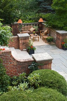 Brick masonry walls and steps form a structured garden in the midst of a heavily wooded property.  Bullnosed column coping and brick wall coping top the garden walls, while a limestone balustrade surrounds a seating niche overlooking the surrounding woodland.
