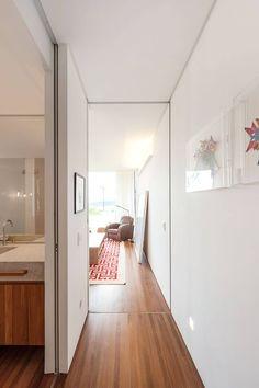 Corredor da suite, piso de madeira, paredes brancas, e quadros na parede. Portas de correto do piso ao teto. Casa Contemporânea em São Paulo por Jacobsen Arquitetura