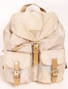 "Prada cream/beige small backpack- Top handle and adjustable back straps. Drawstring underneath front flap; magnetic and buckle closures. Two front flap pockets; buckle closures. This is the perfect stylish backpack for your on-the-go daily look, and will easily hold everything you need for the day. In great condition, with a few tiny spots and smudges. 11"" long, 11"" wide."