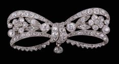 A Belle Epoque diamond bow brooch by Cartier, circa 1910, the ribbon bow with flower head detail set throughout with old cut and rose cut diamonds, approximately 2.80 carats total, signed Cartier Paris.  Estimate £2000–3000