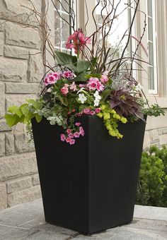 Planter pot for gardeners. Smart variations in color, textures, foliage.  Tall dried twigs for height are a great idea, get a climbing plant to travel up them.