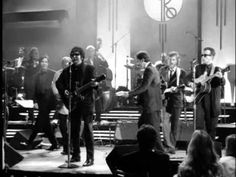 "Roy Orbison performs ""Oh, Pretty Woman"" as the finale of the Black & White Night Concert. Backed by Bruce Springsteen, Elvis Costello, James Burton, Glen D. Hardin, Tom Waits, kd lang, Jackson Browne, Bonnie Raitt, JD Souther, T Bone Burnett, Steven Soles, and Jennifer Warnes. Recorded September 30, 1987."