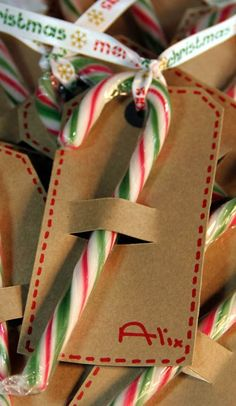 Candy Cane Tags - make 2 slits with a craft knife in brown paper tags, draw a bit of faux stitching around the outside and add candy cane and some ribbon! Crafty Ribbons | Day 11 - Table Tags