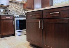Photo gallery of remodeled kitchen features CliqStudios Dayton Cherry Russet cabinets and glass tile backsplash