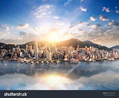 Hong Kong City Skyline View From Harbor With Skyscrapers Buildings Reflect In Water At Sunset With Sunlight And Sun Rays Shine Through Clouds On Blue Sky Стоковые фотографии 326904785 : Shutterstock