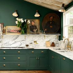 Kitchen with forest green cabinents, marble countertops, gold fixtures, and vintage art