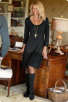 Black sweater dress, trimmed with five tiers of soft, loopy fringe.