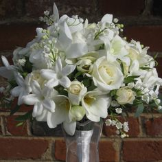A wired posy of stephanotis, lily of the valley, white spray roses and white freesia