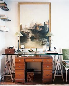 Work Space - A large framed artwork above a wooden desk and a glass-topped sawhorse table