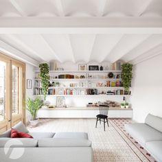 Przestronny salon w bieli z zabudowaną domową biblioteczką na węższej ścianie i... bardzo oryginalnym sufitem! Rośliny doniczkowe w intensywnej zieleni wnoszą naturalność, a duże okna w przyjemny sposób rozjaśniają wnętrze.
