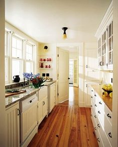 Galley Kitchen With White Cabinets, Wood Floors, Granite Counters, Glass In  Uppers