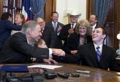 Gov. Greg Abbott, l, shakes hands with student Zachariah Moccia, 25, of San Antonio after signing SB 339, allowing limited medical use of marijuana-derived oils that help control seizures in epileptic patients on June 1, 2015.