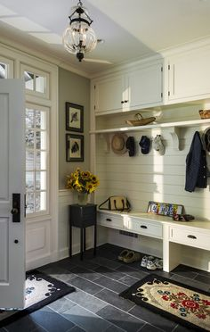 Built-in entry mudroom in the foyer with shiplap, bench seating, cabinets, and coat hooks. Farmhouse style entry way design, decor and remodel ideas.