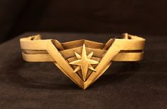 How does Wonder Woman keep her tiara on in battle?   Most of the replicas on the internet seem to be rigid half crowns or fabric design...