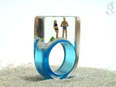 Summer breeze – summerlike beach figure ring with mini-figures, frog and sand on lightblue ring made of resin  ///// © Isabell Kiefhaber www.geschmeideunterteck.de