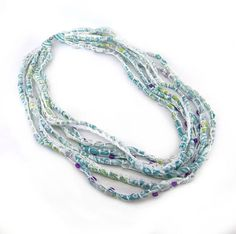 A perfect necklace for spring and summer!  Made of 6 layers of lightweight white Chiffon fabric with touches of turquoise, lime green and purple and finished with clear and purple glass beads.   This necklace measures 27 inches at the shortest layer and 33 inches at the longest layer and secured with a small brass magnetic clasp.  Please contact me with any question or requests. I can make something for you in your choice of colors.  I hand sew each necklace in my pet free and smoke free…