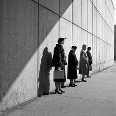 Vivian Maier - I like all the straight lines (the people in the line, lines on the wall, and the line of the shadow)