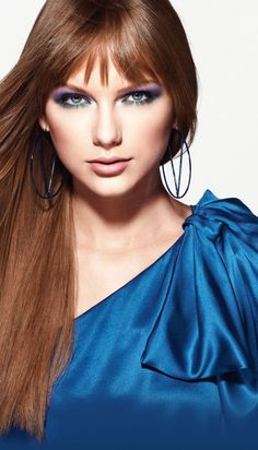 Taylor Swift has red brunette brown hair, blue eyes and she is wearing her royal blue dress.